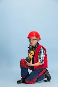 Chłopiec ubrany w czerwony hełm i trzymając wiertło