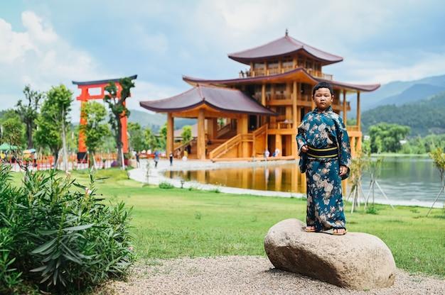Chłopiec ubrany w kimono stoi pośrodku japońskiego miasta modelowego.