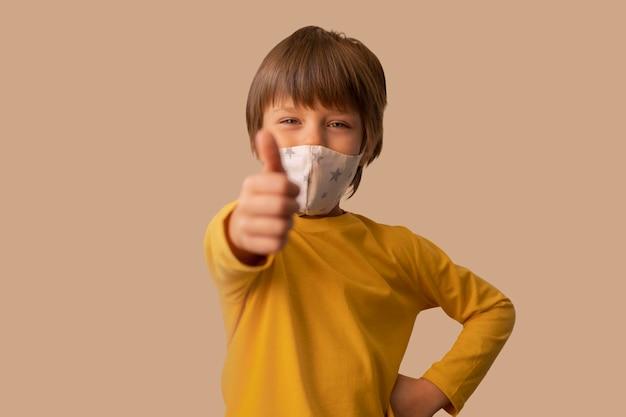 Chłopiec ubrany w maskę medyczną i pokazujący znak ok