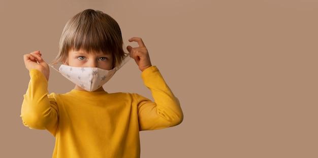 Chłopiec ubrany w maskę medyczną z miejsca na kopię