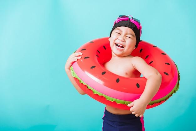 Chłopiec ubrany w strój kąpielowy, trzymając plażowy nadmuchiwany pierścień arbuza