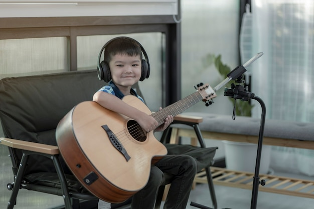 Chłopiec uczący się gry na gitarze, koncentracja na graniu muzyki,