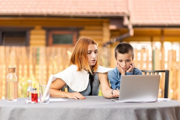 Chłopiec uczący się w domu w klasie online w przydomowym ogrodzie. uczeń słucha wykładu i rozwiązuje problemy