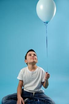 Chłopiec uczeń siedzi na niebieskiej powierzchni i patrzy na niebieski balon