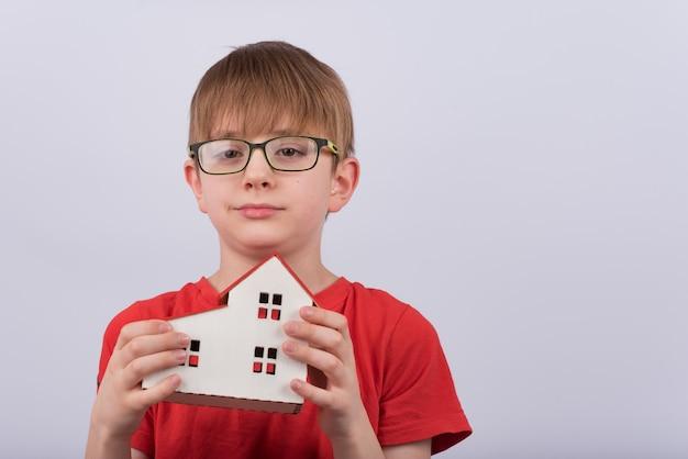 Chłopiec uczeń trzyma model domu. koncepcja nauczania w domu.
