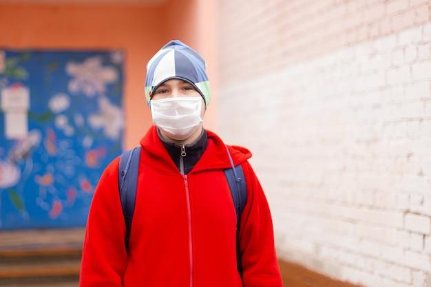 Chłopiec-uczeń wychodzi ze szkoły w masce ochronnej
