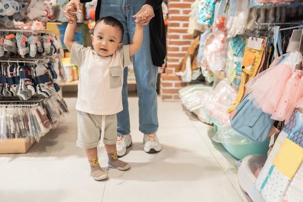 Chłopiec uczy się chodzić podczas zakupów w sklepie dla dzieci