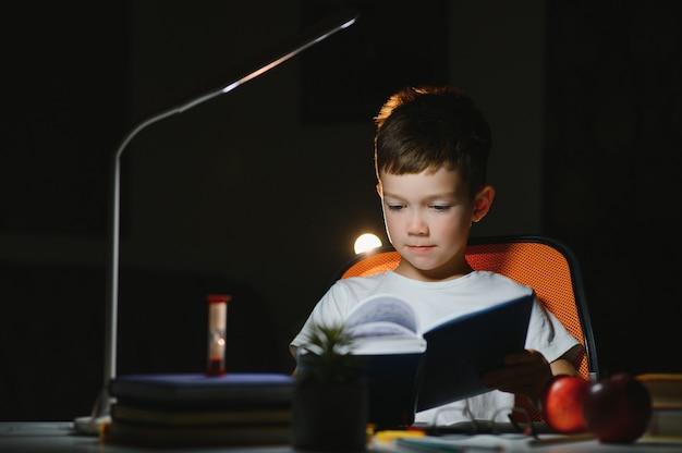 Chłopiec uczy się lekcji w domu, przy stole w świetle lampy stołowej.