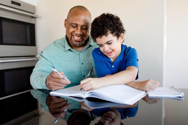 Chłopiec uczy się w domu od swojego ojca w nowej normalności