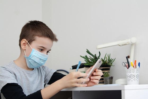 Chłopiec uczy się w domu ze smartfonem w ręku i maską medyczną. koncepcja kwarantanny koronawirusa