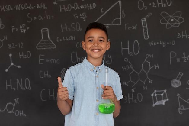 Chłopiec uczy się więcej o chemii w klasie