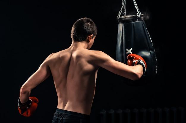 Chłopiec uderza uderza pięścią torbę na ciemnym tle
