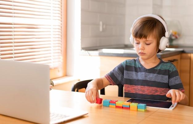 Chłopiec układający zabawki w szkole w internecie