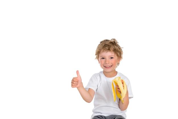 Chłopiec unoszący kciuk dłoni wskazując, że je słodkiego banana.