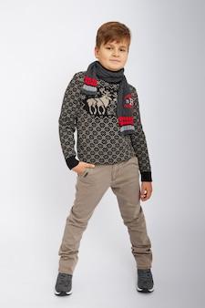 Chłopiec uśmiecha się i pozuje na białej ścianie w studio, moda i ubrania.