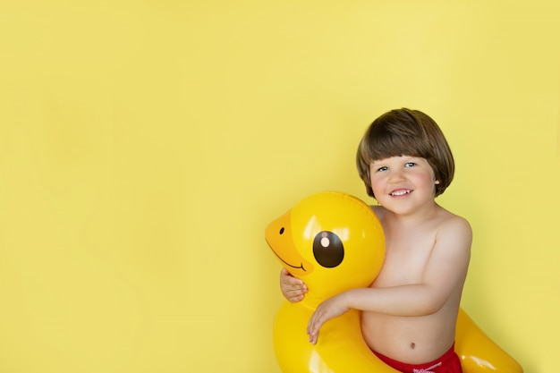 Chłopiec uśmiecha się żółtej kaczki basenu nadmuchiwanego pływającego pływaka z kopii przestrzenią na żółtym tle i ściska