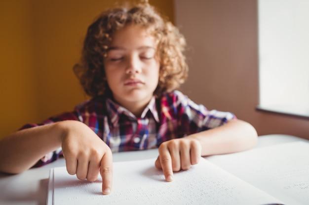 Chłopiec używa braille'a do czytania