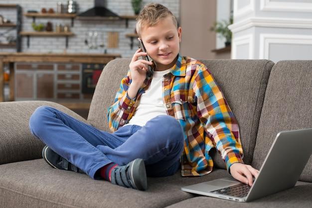 Chłopiec używa laptop na leżance i robi rozmowie telefonicza