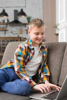 Chłopiec używa laptop na leżance