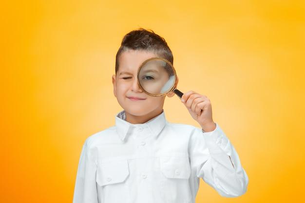 Chłopiec używa magnifier przyglądającego zakończenie up