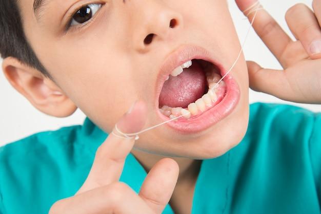 Chłopiec używa stomatologicznego floss czyścić ząb