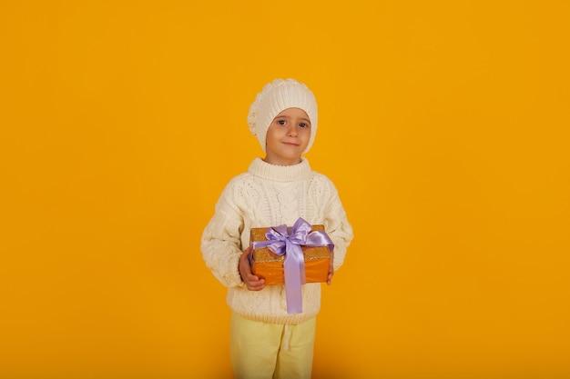Chłopiec w białej czapce zimowej w białym swetrze z dzianiny trzyma w rękach pudełko na prezent