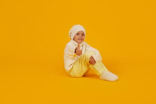 Chłopiec w białej czapce zimowej w dzianym białym swetrze i skarpetkach na żółtym tlebiałym