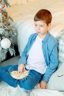 Chłopiec w białej koszulce i dżinsowej koszuli chłopiec w domu z popcornem czas w domu na oglądanie filmu w swoim pokoju weekendy