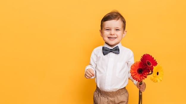 Chłopiec w białej koszuli, spodniach i muszce trzyma bukiet gerber.