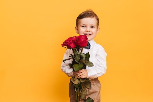 Chłopiec w białej koszuli, spodniach i muszce trzyma w rękach bukiet czerwonych róż. prezent dla mojej mamy