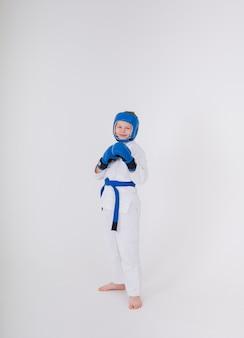 Chłopiec w białym kimonie, sportowy kask, rękawice bokserskie stoi w pozie na białym tle
