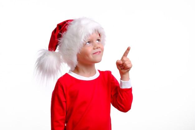 Chłopiec w boże narodzenie santa hat wskazuje palcem