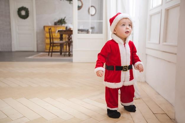 Chłopiec w bożenarodzeniowej kostiumowej pozyci w pokoju