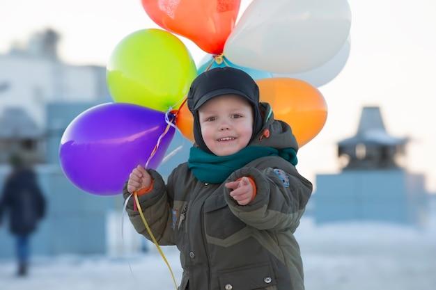 Chłopiec w ciepłych ubraniach z kolorowymi dmuchanymi piłkami zimą