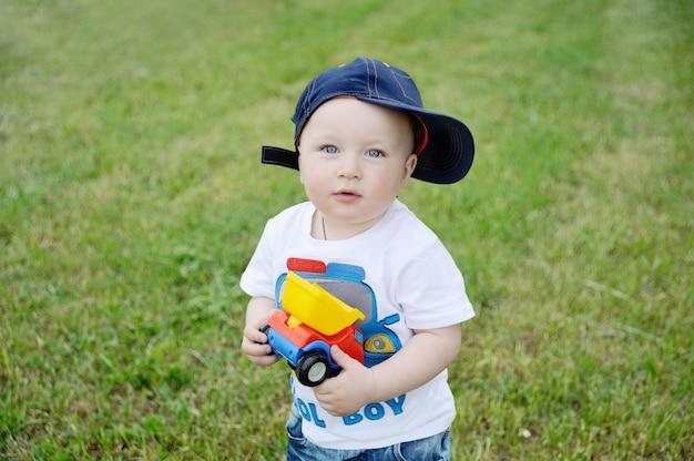 Chłopiec w czapce i samochodzik w rękach