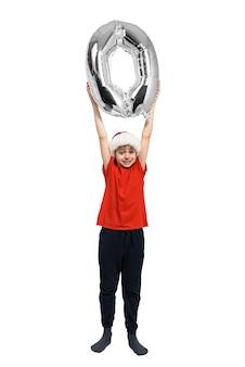 Chłopiec w czapce mikołaja trzyma nad głową srebrne nadmuchiwane zero. białe tło. koncepcja nowego roku