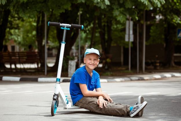 Chłopiec w czapce siedzi na skuterze w parku w słoneczny letni dzień