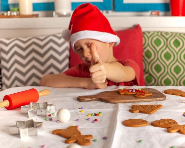 Chłopiec w czapce świętego mikołaja trzyma kciuki w górze, otoczony świątecznymi ciasteczkami
