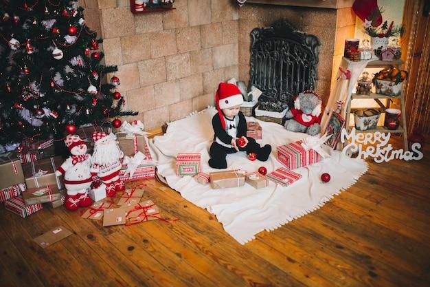 Chłopiec w czapce świętego mikołaja w świątecznym wystroju na wakacje trzyma piłeczkę na choince