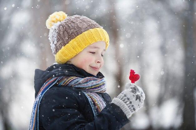 Chłopiec w czapce z żółtym pomponem spaceruje w śnieżny zimowy dzień