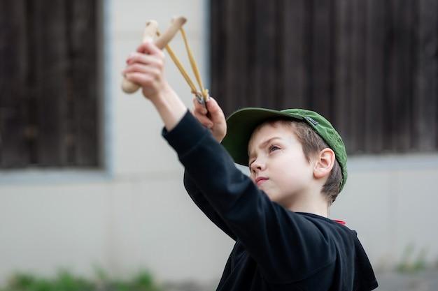 Chłopiec w czarnej kurtce z kapturem i czapką strzela z procy