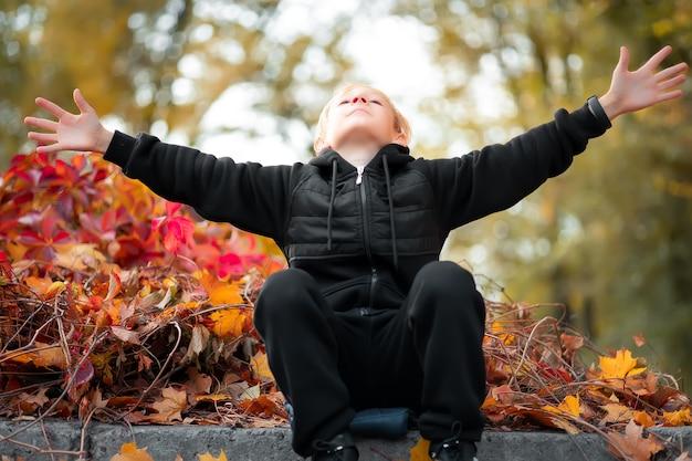 Chłopiec w czarnych ubraniach na tle jesiennego parku rozłożył ręce na boki.
