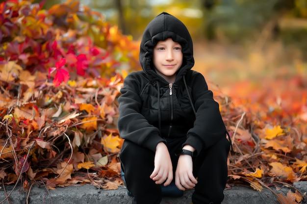 Chłopiec w czarnym kapturze i kurtce siedzi na brzegu na tle jesiennego krzewu.