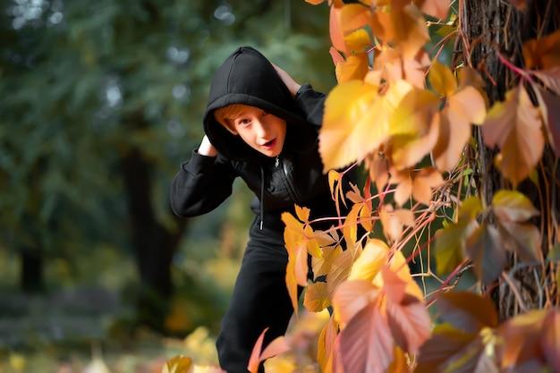 Chłopiec w czarnym kapturze i kurtce stoi za drzewem pokrytym liśćmi.