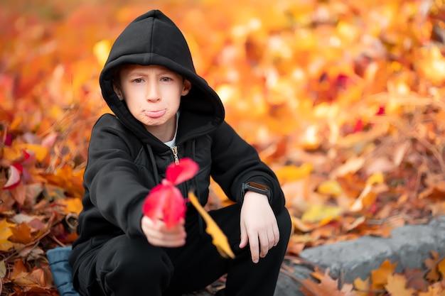 Chłopiec w czarnym swetrze z kapturem wyciąga do aparatu jesienny liść