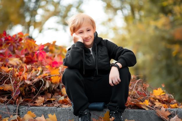 Chłopiec w czarnym ubraniu przycisnął dłoń do policzka, siada i nudzi się.