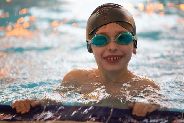 Chłopiec w czepku i okularach pływackich w basenie