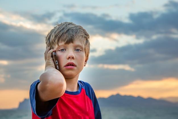 Chłopiec w czerwonej koszulce siedzi na zewnątrz i rozmawia przez telefon komórkowy, wygląda na zdenerwowanego lub przestraszonego