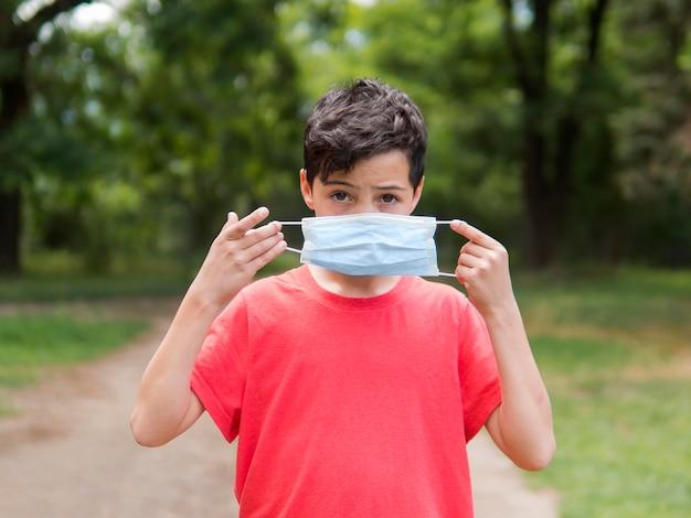 Chłopiec w czerwonej koszuli noszenie maski medyczne