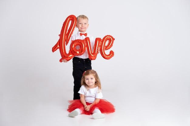 Chłopiec w czerwonej muszce trzyma napis miłość z balonów i małą dziewczynkę siedzącą obok niego.